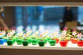 Muitas flores de plástico colorido brinquedo na montra de vidro. — Foto Stock