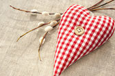 Homemade sewed red cotton love heart with spring willow twig — Stock Photo