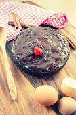 Round homemade chocolate cake on wooden background with retro fi — Stockfoto