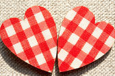Two red checkered love hearts on burlap background. — Stock Photo