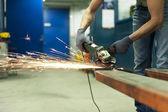 Člověk ruce řezání kovu s jiskry v dílně. obrábění kovů. — Stock fotografie