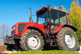 Modern red tractor on a blue sky background — Stock Photo