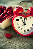 Red heart shaped clock with sweet chocolates — Stock Photo