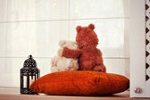 Two embracing loving teddy bears sitting on window-sill. — Stock Photo