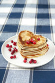 Heart shaped pancakes with cranberries on porcelain plate. Close — Stock Photo
