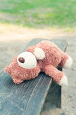 Lonely forgotten teddy bear toy lying on the bench. — Stock Photo