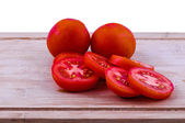 Chopped and whole tomatoes on chopping board — Stock Photo