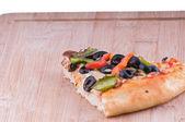 Pizza slice on chopping board — Stockfoto