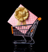 Shopping Cart with gift box isolated in black — Stock Photo
