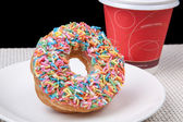 Colorful Donut in white plate and coffee with black background — Stock Photo