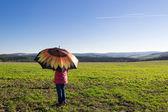 Girl under a sunshade walking in farmland — Stock Photo