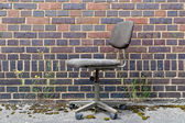 Office chair in front of brick wall — Foto de Stock