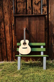 Guitar on a wooden bench — Stock Photo
