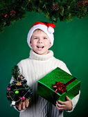Surprised smiling boy in Santa hat with present. New Year. Christmas. — Stock Photo