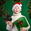 Surprised funny boy in Santa hat with present. New Year. Christmas. — Stock Photo