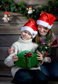 Smiling children with Christmas gift and New Year tree. Making a present. — Stock Photo