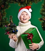 Surprised funny boy in Santa hat with present. New Year. Christmas. — Stock fotografie