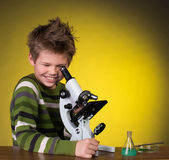 The boy with a microscope and colorful flasks on a yellow background. — Stock Photo