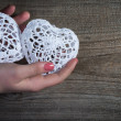 Woman hands holding white lace hearts on old wood background. Valentine's day. — Stock Photo