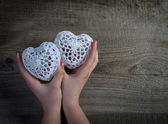 Woman hands holding white lace hearts on old wood background. Valentine's day. — Stock fotografie