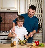 Father and son preparing vegetable salad in the kitchen. — Foto de Stock