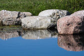 Background with rocks reflecting in the blue water — Stock Photo