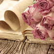 Dry roses on an old book — Stock Photo