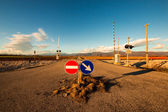 Railroad crossing with mountains behind — Стоковое фото