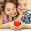 Little boy and girl holding in hands red heart — Stock Photo