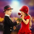 Lovely little boy giving a rose to girl — Stock Photo #38869653