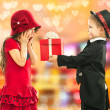 Little boy giving girl gift and his excited — Stock Photo