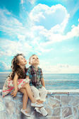 Children looking blue sky with heart shaped clouds — Stock Photo