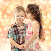Little girl whispering something to boy — Stock Photo