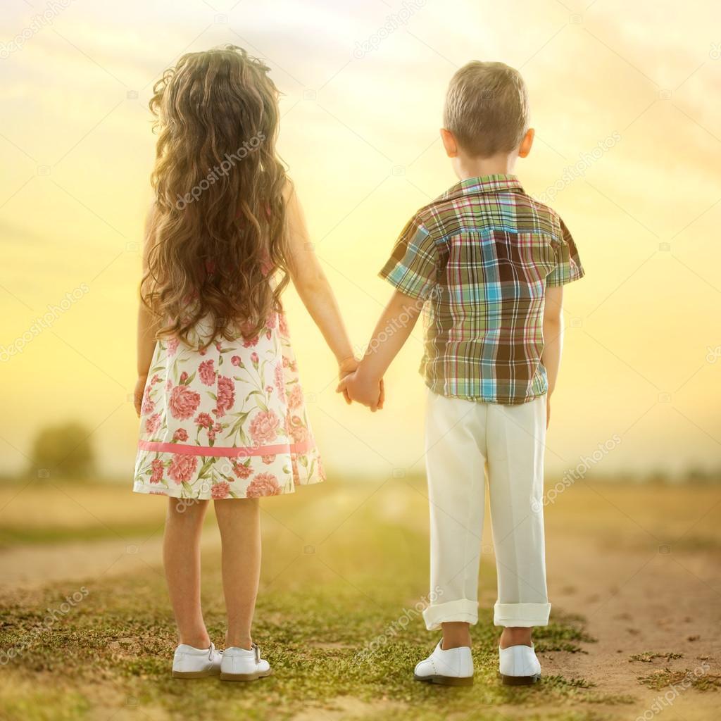 Little Kids Holding Hands On The Beach
