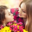 Daughter kissing happy mother with flowers — Stock Photo