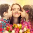 Happy mother kissed by her daughter and son — Stockfoto