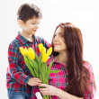 Son hugging his mother and gives her flowers — Stock Photo #41855587