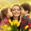 Happy mother kissed by her daughter and son — Stock Photo #41855605