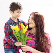 Son hugging his mother and gives her flowers — Stock Photo