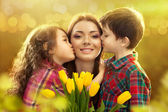 Happy mother kissed by her daughter and son — Fotografia Stock