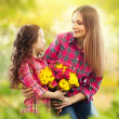 Daughter hugging his mother and gives her flowers — Stock Photo
