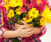 Girl hand is holding a bouquet of flowers — Stock Photo