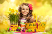 Happy little girl with easter rabbit and eggs — Stock Photo