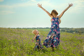 Happy mother and daughter standing in field — Stock Photo