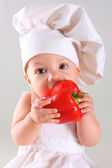 Little baby in a cap chef with Pepper — Stock Photo