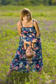 Happy mother playing with daughter in field — Stock Photo