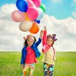 Children with balloons walking on spring field — Stock Photo