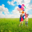 Children with balloons walking on spring field — Stok fotoğraf