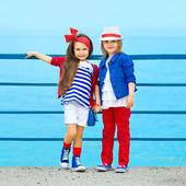 Fashion kids resting on the sea — Stock Photo