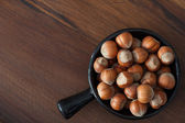 Hazel nuts in black bowl on wooden table — Stock Photo
